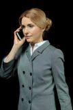 Femme d'affaires blonde dans le tenue de soirée parlant sur le smartphone Photographie stock libre de droits