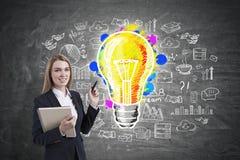 Femme d'affaires blonde de sourire avec un marqueur, ampoule Image libre de droits