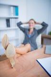 Femme d'affaires blonde de sourire se détendant Photographie stock libre de droits