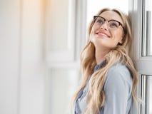 Femme d'affaires blonde enthousiaste appréciant la paix près de la fenêtre Photographie stock