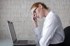 Femme d'affaires blonde futée pensant au bureau Image libre de droits
