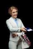 Femme d'affaires blonde heureuse avec le billet de passeport et d'avion dans le costume blanc prêt à se déclencher Photographie stock libre de droits