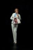 Femme d'affaires blonde heureuse avec le sac dans le costume blanc Photographie stock libre de droits