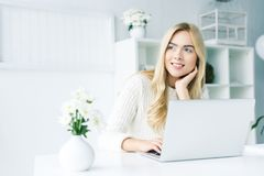 femme d'affaires blonde rêveuse travaillant avec l'ordinateur portable Photographie stock libre de droits