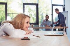 Femme d'affaires blonde regardant l'ordinateur portable tandis que collègues travaillant derrière Images libres de droits