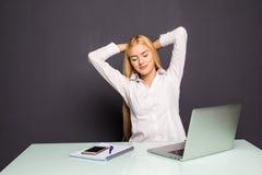 Femme d'affaires blonde regardant le travail sur l'ordinateur portable avec satisfaction et étirant des bras dans le ciel Photo stock