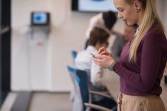 Femme d'affaires blonde tenant le smartphone au bureau Photo stock