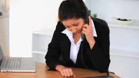 Femme d'affaires bouleversée avec un ordinateur portable et un téléphone banque de vidéos