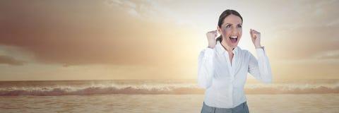 Femme d'affaires célébrant sur la plage de coucher du soleil Images stock