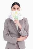 Femme d'affaires cachant son visage derrière des billets de banque Image stock