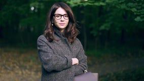 Femme d'affaires calme en verres souriant dans une forêt d'automne clips vidéos