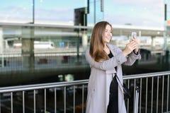 Femme d'affaires caucasienne faisant le selfie par le smartphone près de la mallette et de l'aéroport Photographie stock