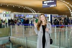 Femme d'affaires caucasienne parlant par le smartphone au hall d'aéroport, au manteau gris de port et montrant correct Photo stock