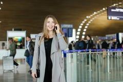 Femme d'affaires caucasienne parlant par le smartphone au hall d'aéroport, au manteau gris de port et au sac Image libre de droits