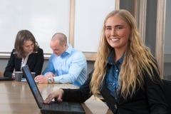 Femme d'affaires caucasienne souriant lors du contact Image stock