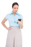 Femme d'affaires chique inquiétée regardant sa calculatrice Images stock