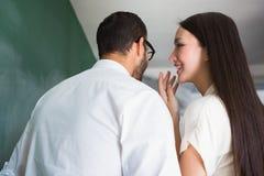 Femme d'affaires chuchotant dans l'oreille masculine de collègues photo stock