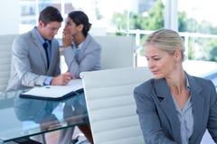 Femme d'affaires chuchotant quelque chose à son collègue Image libre de droits