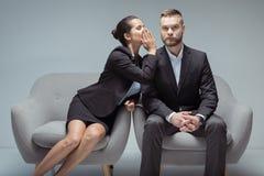 Femme d'affaires chuchotant quelque chose sur l'oreille du ` s de collègue tout en se reposant sur des chaises image libre de droits