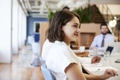 Femme d'affaires With Colleagues Sitting au Tableau écoutant la présentation dans le bureau moderne photos stock