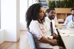 Femme d'affaires With Colleagues Sitting au Tableau ?coutant la pr?sentation dans le bureau moderne photographie stock libre de droits