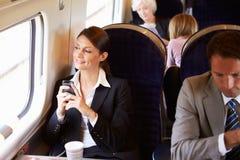 Femme d'affaires Commuting To Work sur le train utilisant le téléphone portable Images libres de droits