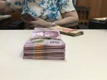 Femme d'affaires comptant une pile de factures d'argent de peso mexicain photos stock