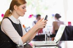 Femme d'affaires concentrée envoyant un texte Images libres de droits