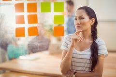 Femme d'affaires concentrée regardant des post-its sur le mur photographie stock libre de droits