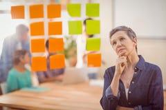 Femme d'affaires concentrée regardant des post-its sur le mur Image libre de droits