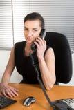 Femme d'affaires concentrée s'asseyant à son fonctionnement et téléphoner de bureau images libres de droits