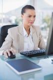 Femme d'affaires concentrée travaillant sur l'ordinateur Images stock