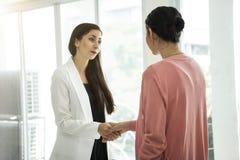 Femme d'affaires concluant l'accord de poignée de main dans le bureau images stock