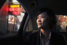 Femme d'affaires contemplative regardant hors de la fenêtre de voiture par la pluie la nuit dans Pékin Photos stock