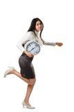 Femme d'affaires courant et tenant une horloge Images stock