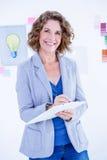 Femme d'affaires créative regardant l'appareil-photo et prenant des notes photos libres de droits