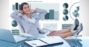 Femme d'affaires décontractée avec des pieds sur le bureau contre des graphiques photo stock