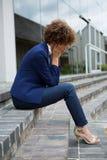 Femme d'affaires déprimée s'asseyant dans les lieux photographie stock