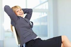 Femme d'affaires détendant sur la présidence Image libre de droits