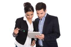 Femme d'affaires d'isolement et homme d'affaires regardant le PC de comprimé. Image stock
