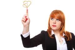 Femme d'affaires d'une chevelure rouge montrant dirigeant le symbole d'amour de coeur Image stock