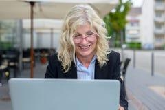 Femme d'affaires d'une cinquantaine d'années travaillant sur son ordinateur portable Photo stock