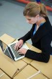 Femme d'affaires dactylographiant sur l'ordinateur portable dans l'entrepôt Photos stock