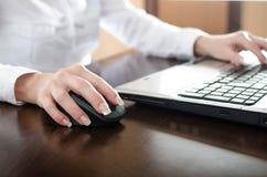 Femme d'affaires dactylographiant sur un ordinateur portable Photographie stock