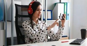 Femme d'affaires dans des écouteurs rouges tirant la vidéo sur le smartphone dans le bureau moderne banque de vidéos