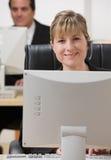 Femme d'affaires dans l'écouteur fonctionnant à l'ordinateur Photographie stock libre de droits