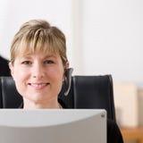 Femme d'affaires dans l'écouteur fonctionnant à l'ordinateur Image stock