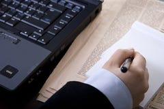 Femme d'affaires dans l'écriture de bureau dans le cahier images stock