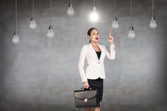 Femme d'affaires dans la chambre avec les ampoules accrochantes Image stock
