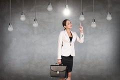 Femme d'affaires dans la chambre avec les ampoules accrochantes Images libres de droits